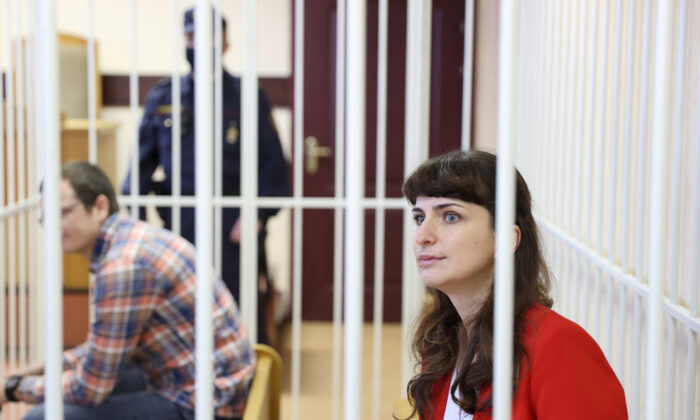 Journalist Katerina Borisevich and doctor Artyom Sorokin sit inside a defendants' cage during a court hearing in Minsk, Belarus, on Feb 19, 2021. (Ramil Nasibulin/BelTA/Handout via Reuters)