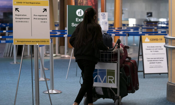 Signage for a new COVID-19 screening centre is pictured at Vancouver International Airport in Richmond, B.C. on February 19, 2021. (Jonathan Hayward/The Canadian Press)