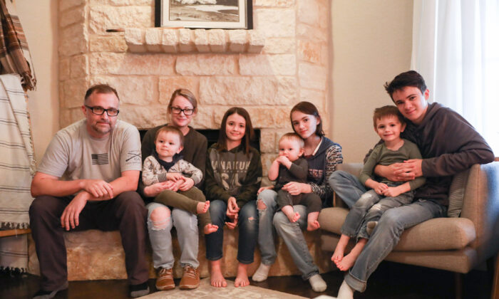 Joel and Christine Williams sit with six of their seven children next to their fireplace in New Braunfels, Texas, on Feb. 25, 2021. (Charlotte Cuthbertson/The Epoch Times)