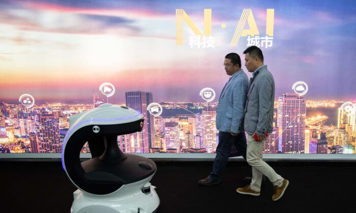 Visitors walk past an AI (artificial intelligence) security robot named APV3 with a facial recognition system at the 14th China International Exhibition on Public Safety and Security at the China International Exhibition Center in Beijing on Oct. 24, 2018. (Nicolas Asfouri/AFP via Getty Images)