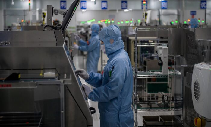 Workers are ween inside the production chain at a semiconductor manufacturing factory in Beijing, China on May 14, 2020. (Nicolas Asfouri/AFP via Getty Images)