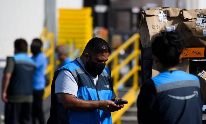 An Amazon delivery driver scans bags of groceries while loading a vehicle outside of a distribution facility in Redondo Beach, Calif., on Feb. 2, 2021. (PATRICK T. FALLON/AFP via Getty Images)