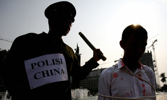 A reenaction of the persecution of Falun Gong practitioners in China. (Adek Berry/AFP via Getty Images)