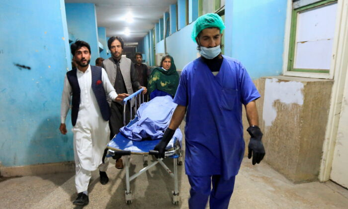 Afghan men transport the body of one of three media workers who were killed by an unknown gunmen, at a hospital in Jalalabad, Afghanistan, on March 2, 2021.   (Parwiz/Reuters)