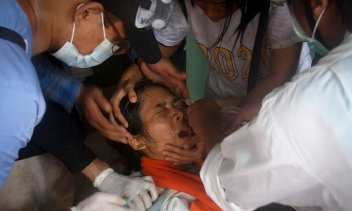 A woman is treated by nurse as she got  hit by tear gas during an anti-coup protest in Yangon, Burma, on March 2, 2021. (AP Photo)