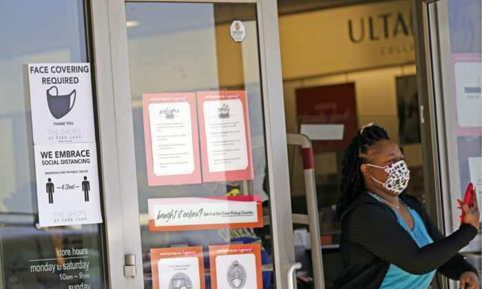 A customer exits a store with a mask required sign displayed in Dallas, Texas on March 2, 2021. (LM Otero/AP Photo)