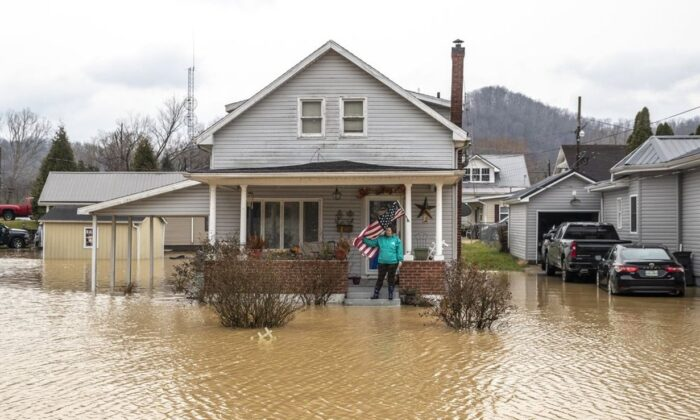 Catherine Castle stands on the porch of her home in downtown Paintsville, Ky., as floodwaters approach on March 1, 2021. (Ryan C. Hemens/Lexington Herald-Leader via AP)