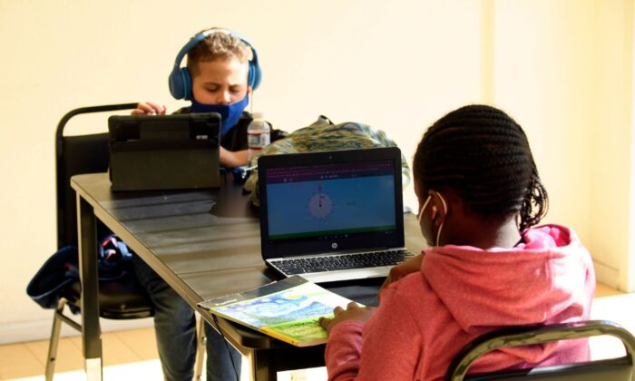 Children attend online classes at a learning hub inside the Crenshaw Family YMCA in Los Angeles on Feb. 17, 2021. (Patrick T. Fallon/AFP via Getty Images)
