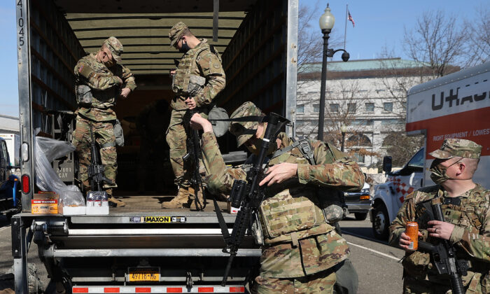 Members of the U.S. National Guard collect long guns from storage vehicles before beginning their shift protecting the U.S. Capitol in Washington on Feb. 8, 2021. (Chip Somodevilla/Getty Images)
