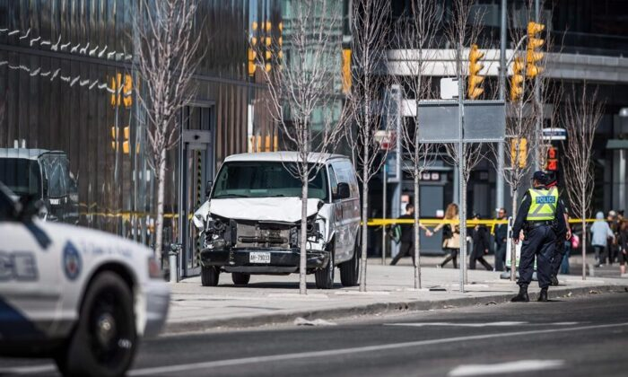 Police on scene after a van driven by Alek Minassian mounted a sidewalk and crashed into a number of pedestrians, in Toronto, on April 23, 2018.