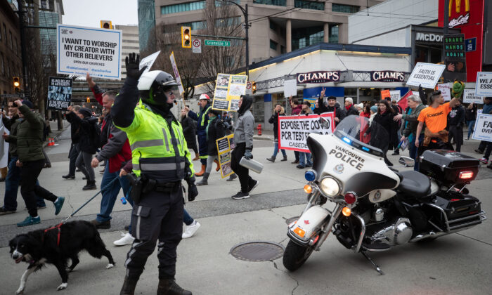 A police officer stops traffic as people opposed to public health measures to curb the spread of COVID-19 march on Granville Street after the B.C. Grand Freedom Rally, in Vancouver, on Saturday, February 20, 2021. THE CANADIAN PRESS/Darryl Dyck