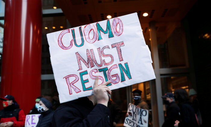 Demonstrators hold signs as they gather outside the New York Gov. Andrew Cuomo's office calling for his resignation, in the Manhattan borough of New York on March 2, 2021. (Shannon Stapleton/Reuters)