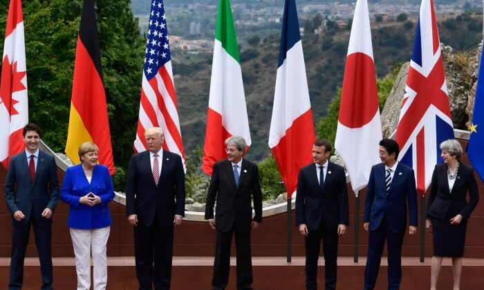 From left: Canadian PM Justin Trudeau, German Chancellor Angela Merkel, U.S. President Donald Trump, Italian PM Paolo Gentiloni, French President Emmanuel Macron, Japanese PM Shinzo Abe, and Britain's PM Theresa May, pose for a family photo at the ancient Greek Theatre of Taormina during the Heads of State and of Government G7 summit in Sicily on May 26, 2017. (Miguel Medina/AFP via Getty Images)