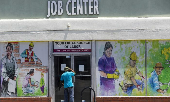 A man looks inside the closed doors of the Pasadena Community Job Center during the coronavirus outbreak in Pasadena, Calif., on May 7, 2020. (Damian Dovarganes/AP Photo)
