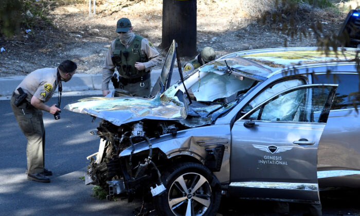 Los Angeles County Sheriff's Deputies inspect the vehicle of golfer Tiger Woods, who was rushed to hospital after suffering multiple injuries, after it was involved in a single-vehicle accident in Los Angeles, California, U.S.  on Feb. 23, 2021.  (Gene Blevins/Reuters)