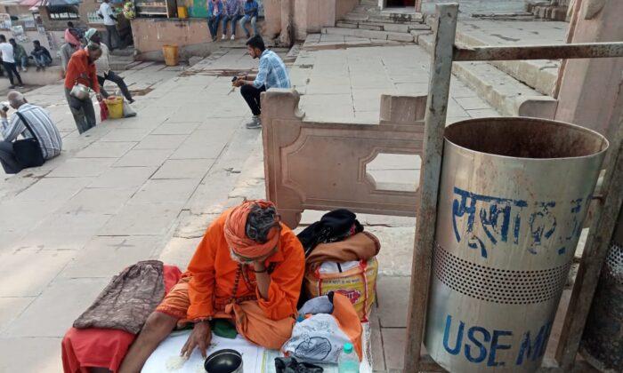 A monk sits on the bank of the river Ganges at the Dashashwamedh ghat  seeking alms in Varanasi on Feb. 19, 2021. (Venus Upadhayaya/Epoch Times)