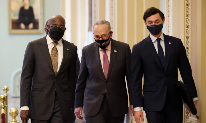 Senate Majority Leader Charles Schumer (D-N.Y.) (C) walks with Sen. Raphael Warnock (D-Ga.) (L) and Sen. Jon Ossoff (D-Ga.) on their way to a news conference at the U.S. Capitol on Feb. 11, 2021. (Chip Somodevilla/Getty Images)