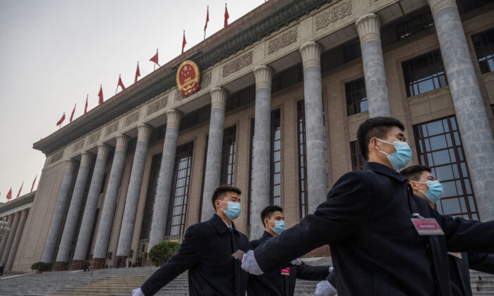 Chinese security wear protective masks as they march after the opening session of the Chinese People's Political Consultative Conference at the Great Hall of the People in Beijing, China, on March 4, 2021. (Kevin Frayer/Getty Images)