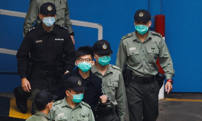 Pro-democracy activist Joshua Wong walks to a prison van to head to court with other activists, over a national security law charge, in Hong Kong, China, on March 4, 2021. (Tyrone Siu/Reuters)