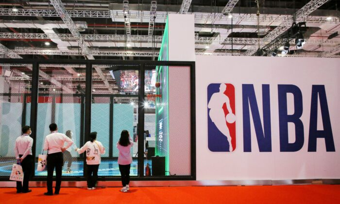 People stand next to an NBA logo at the NBA Exhibition at the 3rd China International Import Expo (CIIE) in Shanghai on Nov. 5, 2020. (STR/AFP via Getty Images)