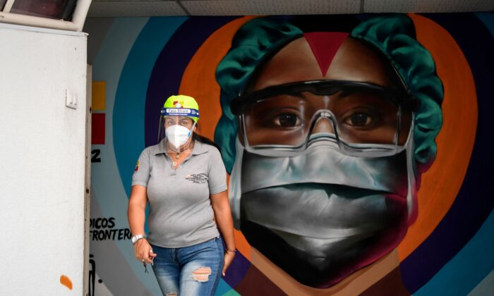 A health worker walks in front of a mural in Caracas, Venezuela, on March 4, 2021. (Yuri Cortez/AFP via Getty Images)