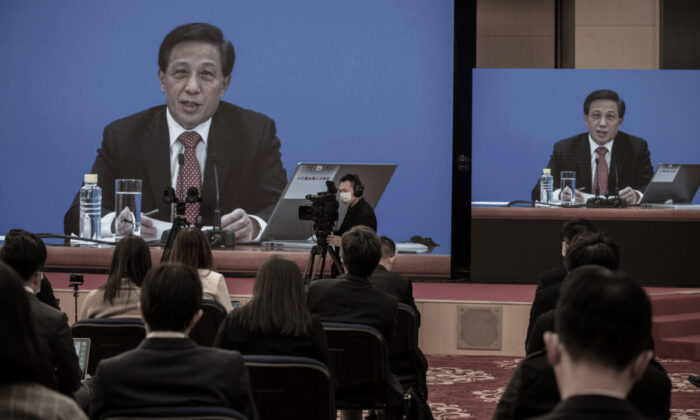 National People's Congress Spokesperson Zhang Yesui is seen on large screens during a video news conference, as a precaution for COVID-19 prevention in Beijing, China, on March 4, 2021. (Kevin Frayer/Getty Images)