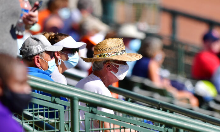 Masked fans look during a spring training game between the Baltimore Orioles and the Boston Red Sox at Ed Smith Stadium in Sarasota, Fla., on March 4, 2021. (Julio Aguilar/Getty Images)