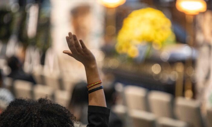 A woman stands and raises her hand as Reverend Al Sharpton gives the eulogy during the memorial service for Andre Hill inside the First Church of God sanctuary in Columbus, Ohio, on Jan. 5, 2021. (Stephen Zenner/AFP via Getty Images)