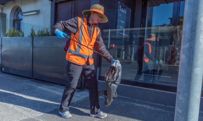 Suzanne Kerr collects street side rubbish in Port Melbourne, Australia, on May 29, 2020. (Asanka Ratnayake/Getty Images)