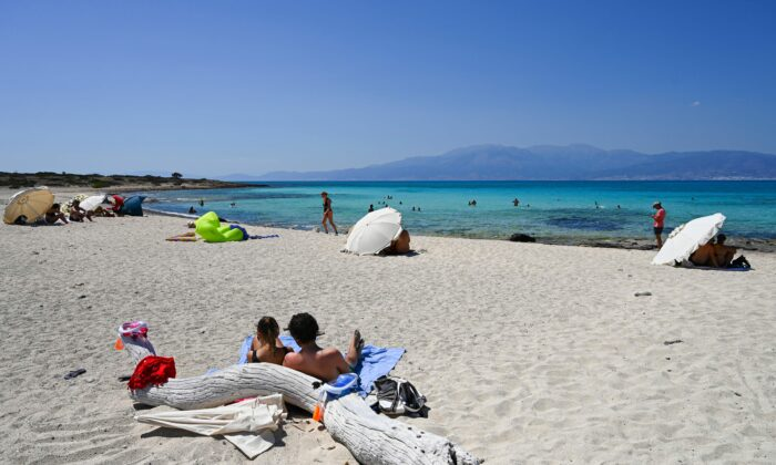 People enjoy the sea on a beach of the small island of Chrysi, south of Crete, on July 26, 2020. (Aris Messinis/AFP via Getty Images)