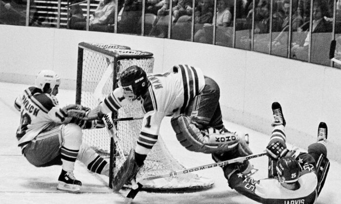 Washington Capitals' Doug Jarvis (25), right, scores a goal against New York Rangers goalie Glen Hanlon during the first period of an NHL hockey game at Madison Square Garden in New York. The puck slides into the goal off the skates of Rangers' Mark Pavelich, left., on Dec. 7, 1983. (Ron Frehm/AP Photo, File)