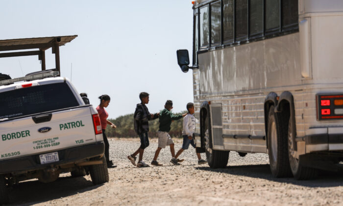 A bus picks up a group of illegal aliens for Border Patrol near the U.S.-Mexico border in Yuma, Ariz., on April 13, 2019. (Charlotte Cuthbertson/The Epoch Times)