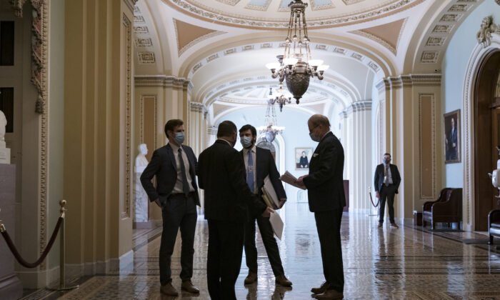 Congressional staffers wait in the ornate corridor outside the Senate chamber during a delay in work on the Democrats' $1.9 trillion COVID-19 relief bill, at the Capitol in Washington on March 5, 2021. (J. Scott Applewhite/AP Photo)
