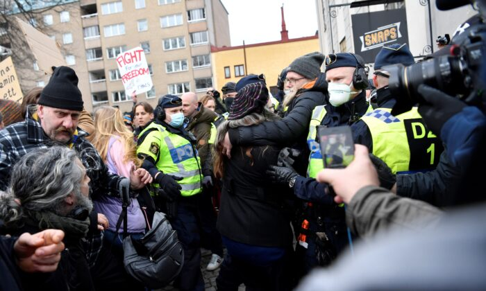 Swedish police break up a demonstration of CCP virus restrictions opponents protesting against a ban on large gatherings, in Stockholm, Sweden, on March 6, 2021. (Henrik Montgomery/TT News Agency via Reuters)