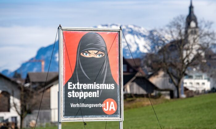 A poster supporting the initiative 'Yes to a ban on covering the face' is displayed at the village Buochs, Switzerland, on Feb. 16, 2021. (Urs Flueeler/Keystone via AP)