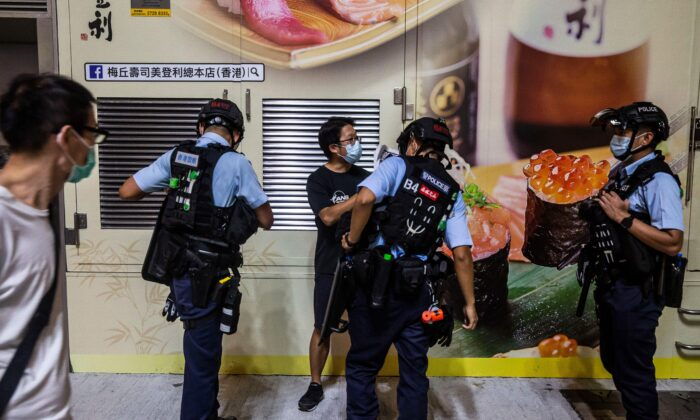 Police conduct an ID check on a man (C) before a planned protest for press freedom in Hong Kong on Aug. 11, 2020, a day after authorities conducted a search of the Apple Daily newspaper's headquarters after the company's founder Jimmy Lai was arrested under the new national security law. (Isaac Lawrence/AFP via Getty Images)