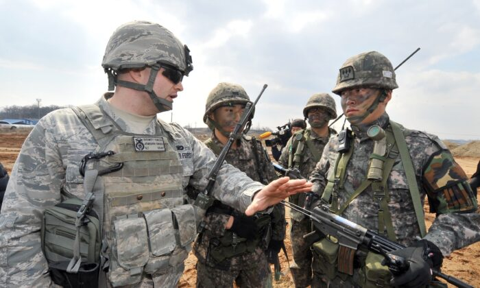 A US Air Force soldier (L) talks to South Korean Army soldiers during an operation to guard a US airbase as part of annual joint exercises outside the airbase in Pyeongtaek, south of Seoul, on March 14, 2013. (Jung Yeon-Je/AFP via Getty Images)