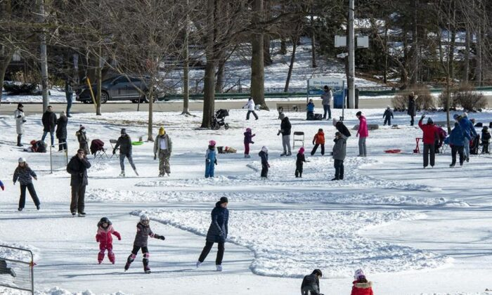 Parents and children enjoy Family Day as they take to the ice on a home made ice rink in a city park in Toronto, on Feb. 15, 2021. Restrictions meant to stem the spread of COVID-19 are easing in parts of Ontario and Quebec and all of New Brunswick. (Frank Gunn / The Canadian Press)