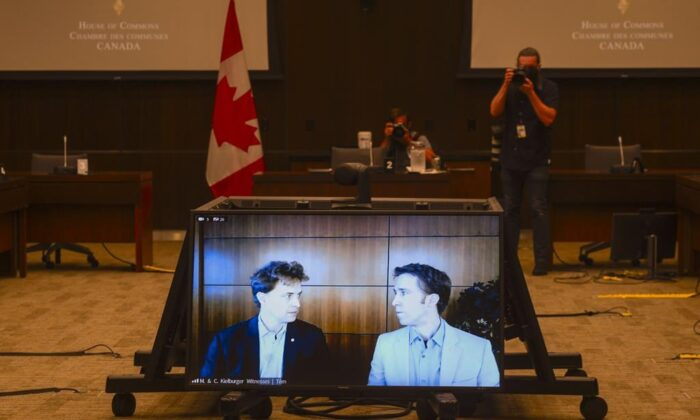 Marc Kielburger, screen left, and Craig Kielburger, screen right, appear as witnesses via videoconference during a House of Commons finance committee in the Wellington Building in Ottawa on July 28, 2020. (Sean Kilpatrick/The Canadian Press)