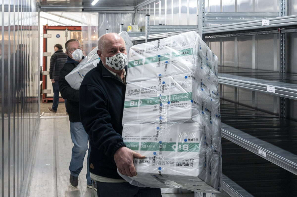 Employees unload the newly arrived coronavirus vaccines from Chinese pharmaceutical company Sinopharm