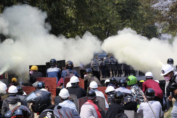 Anti-coup protesters discharge fire extinguishers to counter the impact of the tear gas fired by police