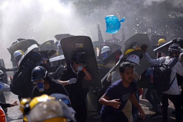 Protesters are dispersed as riot police fire tear gas during a demonstration in Yangon, Myanmar