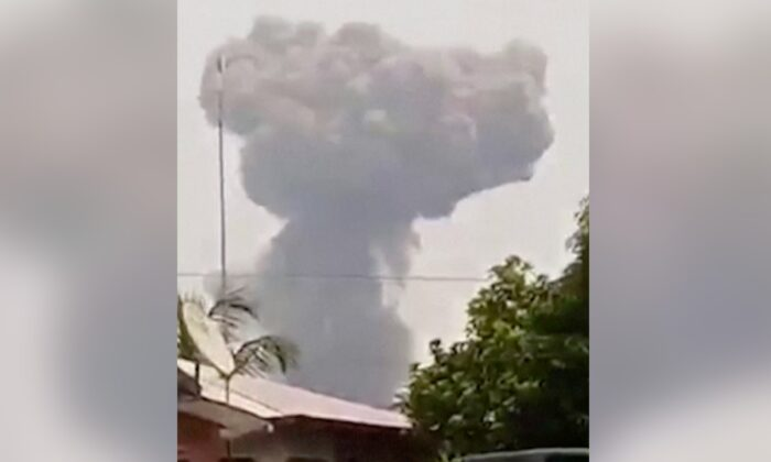 Large cloud of white smoke rising behind a residential building after a series of large explosions at a military base in Bata, Equatorial Guinea, on March 7, 2021. (Screenshot/Courtesy of Modibo Mangoule via Reuters)
