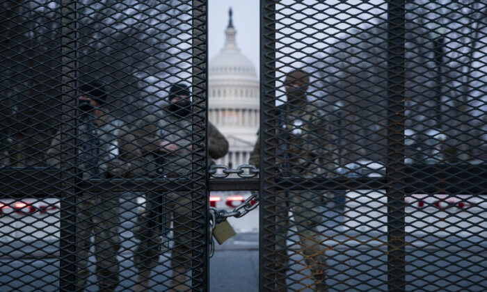Before sunrise, members of the National Guard stand behind a barbed wire fence surrounding the Capitol in Washington on March 4, 2021. (Sarah Silbiger/Getty Images)