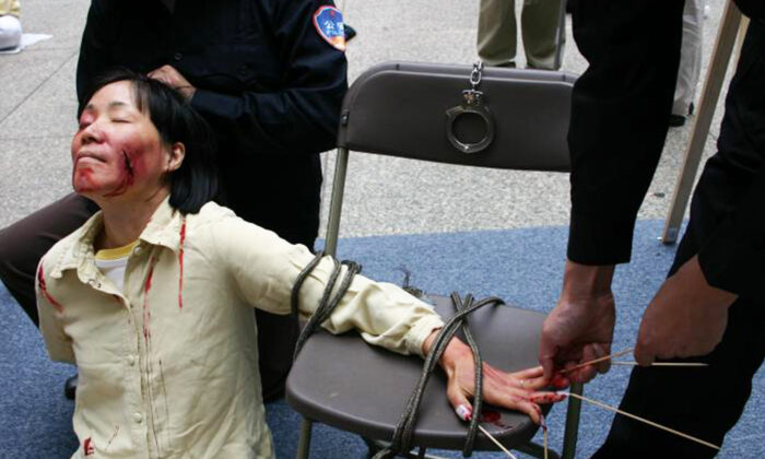 Reenactment of one of the brutal torture methods employed by the CCP officials to coerce female Falun Gong adherents to renounce their faith. (Minghui.org)