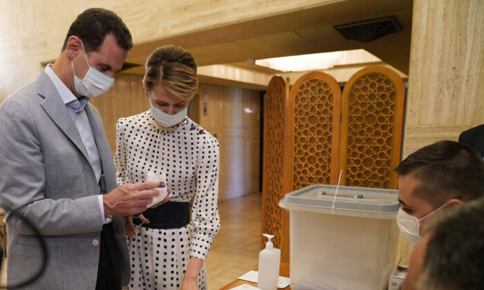 Syrian President Bashar Assad (L) and his wife Asma vote at a polling station in the parliamentary elections, in Damascus, Syria, on July. 19, 2020. (Syrian Presidency via AP)