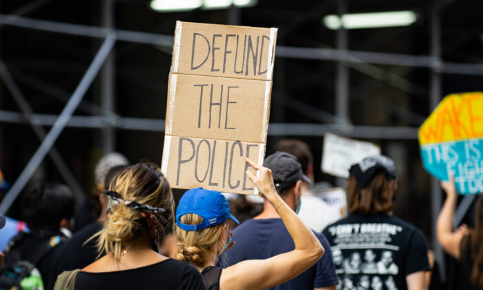 A protester is holding a 'defund the police' sign at a Black Lives Matter protest in Manhattan, New York City on July 13, 2020. (Chung I Ho/The Epoch Times)