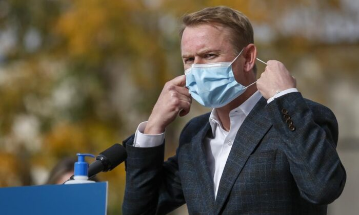 Minister of Health Tyler Shandro, removes his made-in-Calgary mask while announcing a new agreement between Alberta Health Services and a local manufacturer to produce medical equipment, in Calgary, Alta., Oct. 7, 2020. (Jeff McIntosh/The Canadian Press)