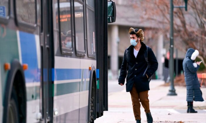 A man in a mask boards a bus on campus at Western University in London, Ontario, Canada, on March 13, 2020. (Geoff Robins/AFP via Getty Images)
