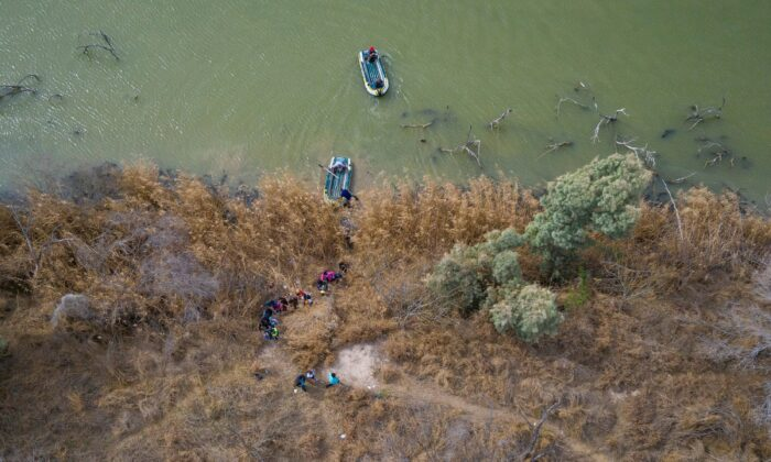 Migrant families and children climb the banks of the Rio Grande River into the United States as smugglers on rafts prepare to return to Mexico in Penitas, Texas, on March 5, 2021. (Adrees Latif/Reuters)